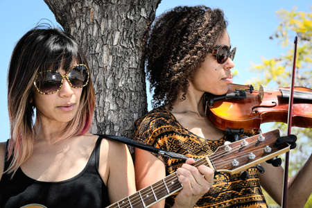 violins: Women musicians playing guitar and violin outdoors Stock Photo