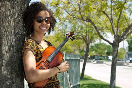 African American woman holding violin and leaning against tree Stock Photo