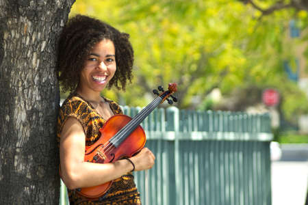 Young biracial violinist smiling and leaning against tree Stock Photo