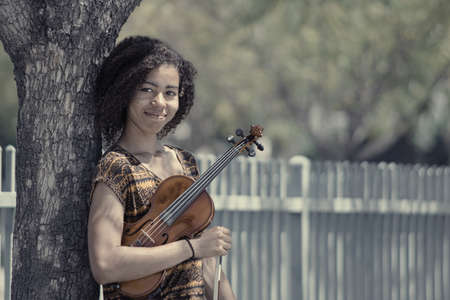 Faded portrait of young woman holding violin outdoors Reklamní fotografie