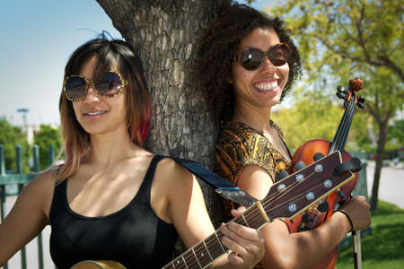 Female guitarist and violinist smiling outdoors