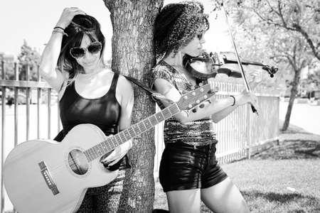 violinista: Mujer violinista y guitarrista se inclina contra �rbol
