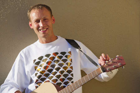 Smiling man musician playing acoustic guitar outdoors