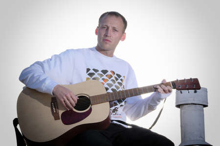 Male guitarist playing acoustic guitar outdoors Stock Photo