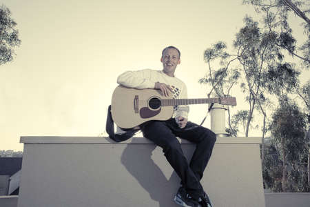 Smiling male musician sitting outside with acoustic guitar Stock Photo