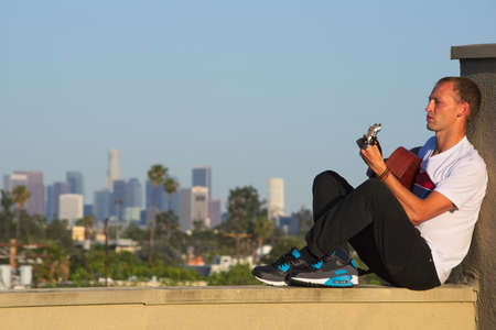 Seated man playing acoustic guitar with LA skyline Stock Photo