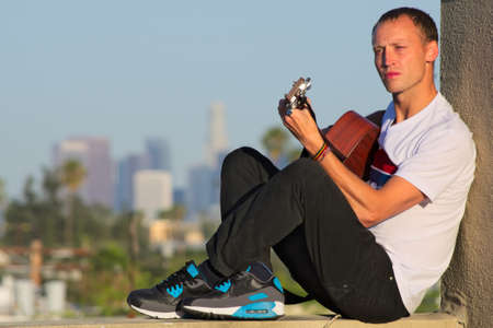 Seated musician playing guitar with LA in background Stock Photo