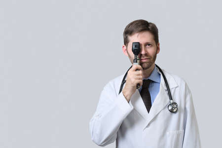 Doctor looking through ophtalmoscope with both eyes open