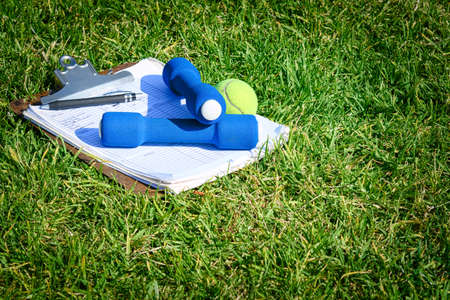 Exercise equipment, tennis ball, and clipboard on grass Stock fotó