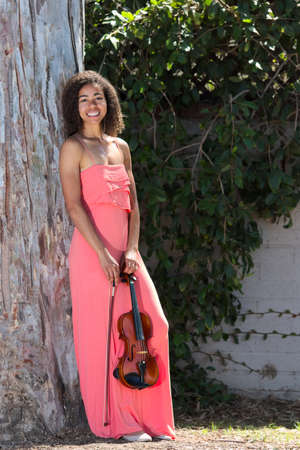 Smiling female violinist in long pink dress outside