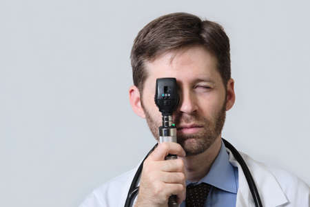 Physician with beard using ophthalmoscope