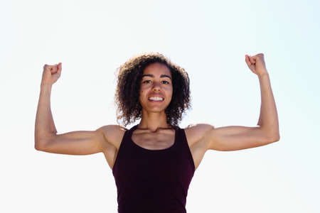 bicep: Strong African American Woman flexing biceps Stock Photo