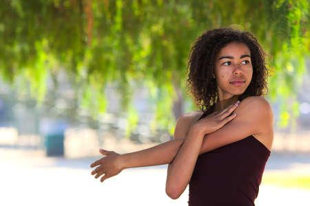 woman stretching: Young woman with curly hair stretching outside