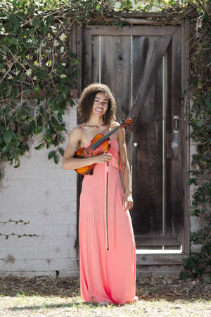 Young woman in pink dress holding violin outside Stock Photo