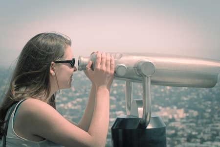 Young woman looking through coin binoculars