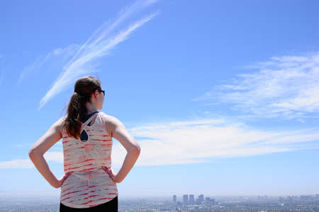 Woman with ponytail looking at city skyline