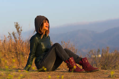Woman with jacket and boots seated on ground laughing Stock Photo