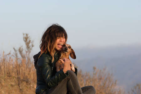 Woman laughing while holding dachshund dog Stock Photo