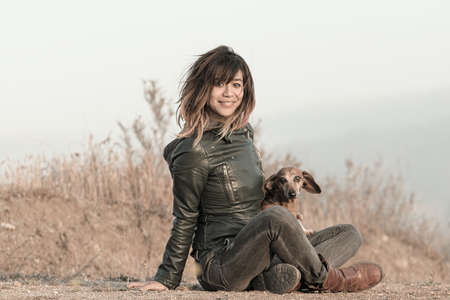 Seated woman with leather jacket and Dachshund Stock Photo