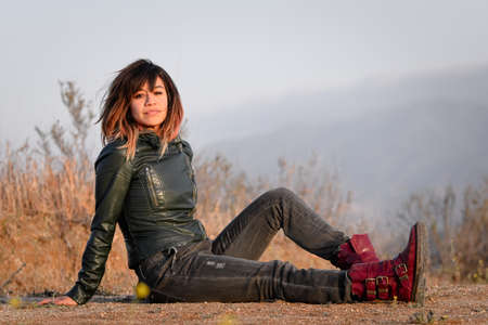smirk: Woman in green leather jacket seated on ground Stock Photo