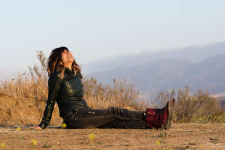 Woman in leather jacket seated on ground laughing
