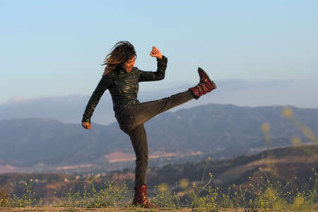 Woman in leather jacket and boots kicking air Stock Photo