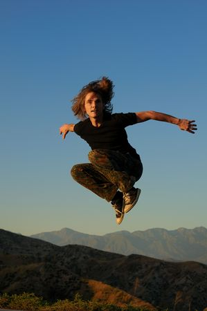 knees up: Caucasian male 20-40 in sportswear jumping above mountain peaks, facing forward, arms widespread, knees up. Stock Photo