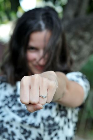 Young, attractive woman punches her hand forward to show off ring.  Selective focus is used.