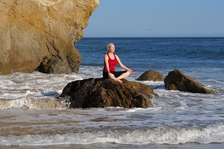 performs: Woman performs yoga meditation on a rock in the surf, facing the sun.