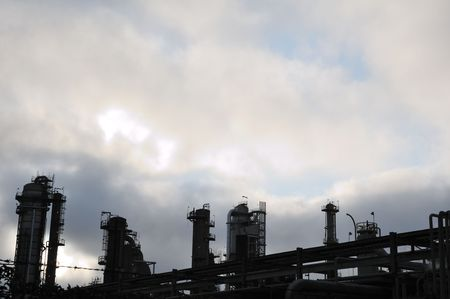 shadowed: Ominous shadowed oil refinery shows a few points of light against a darkening sky.