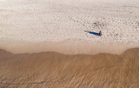 Aerial view of the man sitting on the nice beach from flying drone