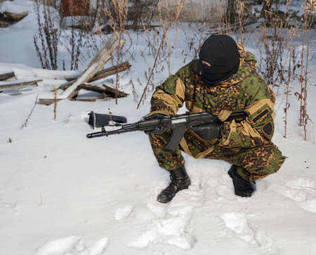 Soldier with AK-47 and a hidden face photo