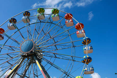 spinning wheel: A colorful big fun wheel against blue sky Stock Photo