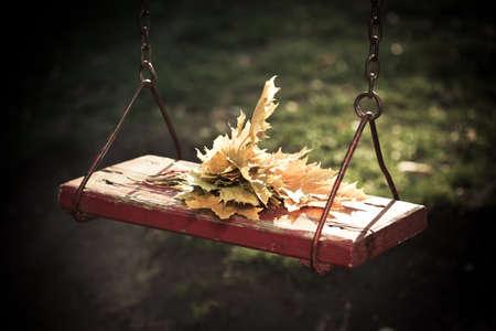 swing seat: Autunno dorato lascia bouquet su un dondolo Archivio Fotografico