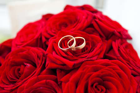 Wedding rings on red roses wedding bouquet photo