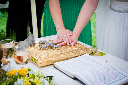 bible altar: Hands on bible at a wedding ceremony