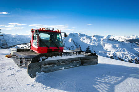 snowcat: Snow-grooming machine on snow hill ready for skiing slope preparations in Austrian Alps
