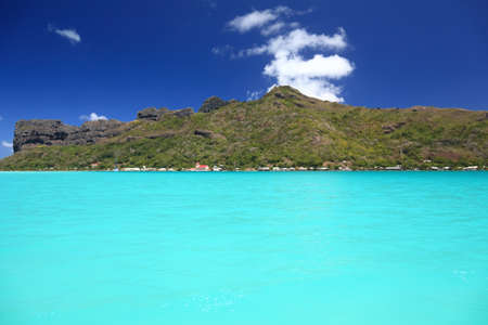south pacific: Dreamlike Colors of the Lagoon in Maupiti, French Polynesia. Maupiti Mainland in Background  Stock Photo
