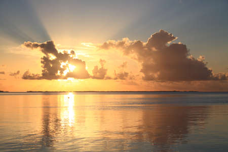 Sunset with Sunbeams at Manihi Atoll in the South Pacific with Coconut Trees  Archivio Fotografico