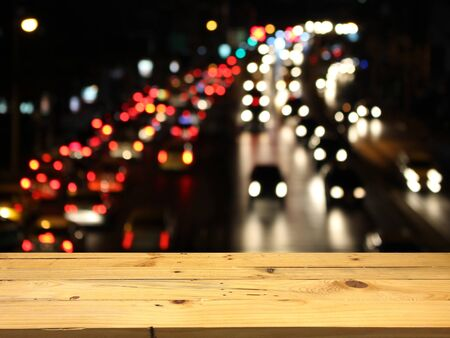 product placement: Wood table for product placement, blurred traffic jam at night background.