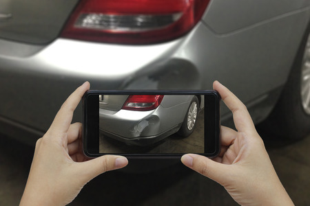 rear end: Hand holding smart phone take a photo at The scene of a car crash, car accident for insurance.