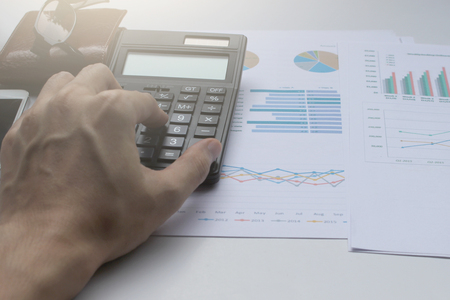 information analysis: Hand use calculator on the office desk  investment and property for concept.