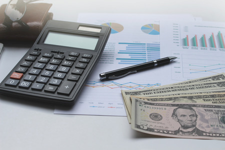 information analysis: Calculator and Dollar money on the office desk investment and property for concept. Stock Photo