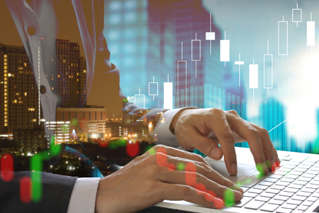 Double exposure of businessman using the laptop with cityscape and stock market or financial graph for financial investment concept on blurred building background. Banque d'images