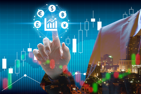 Double exposure of businessman touch virtual currency with cityscape and stock market or financial graph for financial investment concept. Stock Photo