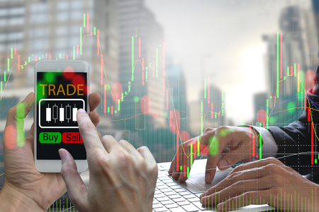 Double exposure of businessman Hand use smartphone and laptop trading online on screen with Candle stick graph chart of stock market and city background.