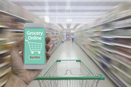 Supermarket aisle with empty shopping cart and Hand use smartphone with grocery online on screen, Supermarket store abstract blurred background with shopping cart.