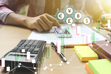 Double exposure of man use smartphone interface of Fintech and Calculator on the office desk with stock market or financial graph for financial investment concept. Stock Photo