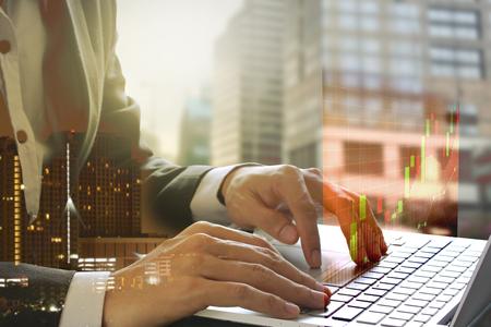 Double exposition d'homme d'affaires utilisant l'ordinateur portable avec graphique boursier ou financier pour le concept d'investissement financier sur fond de bâtiment flou.