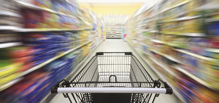 Supermarket aisle with empty shopping cart, Supermarket store abstract blurred background with shopping cart.